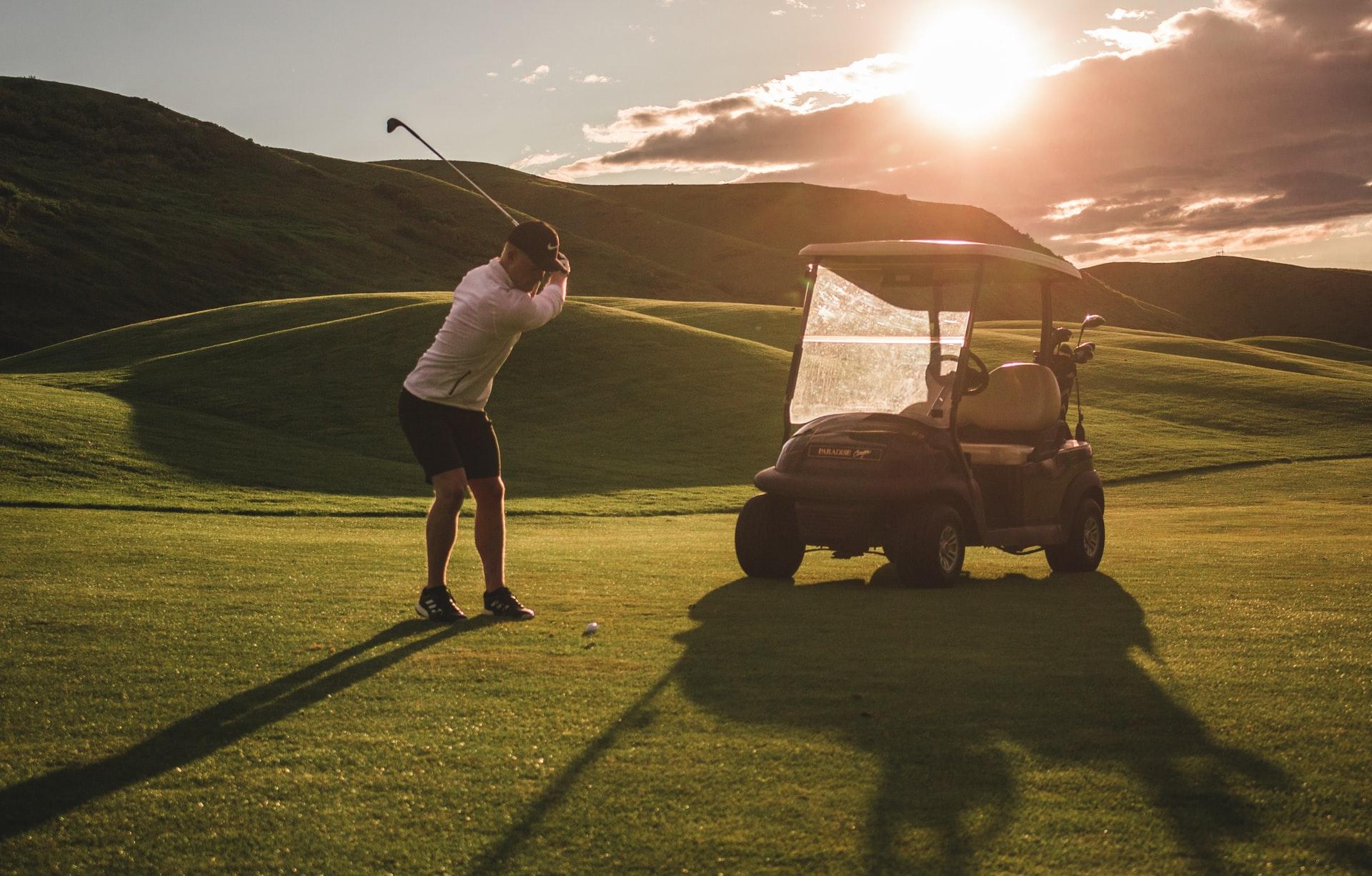 golf cart tax credit 2021 - man golfing at sunset with golf cart