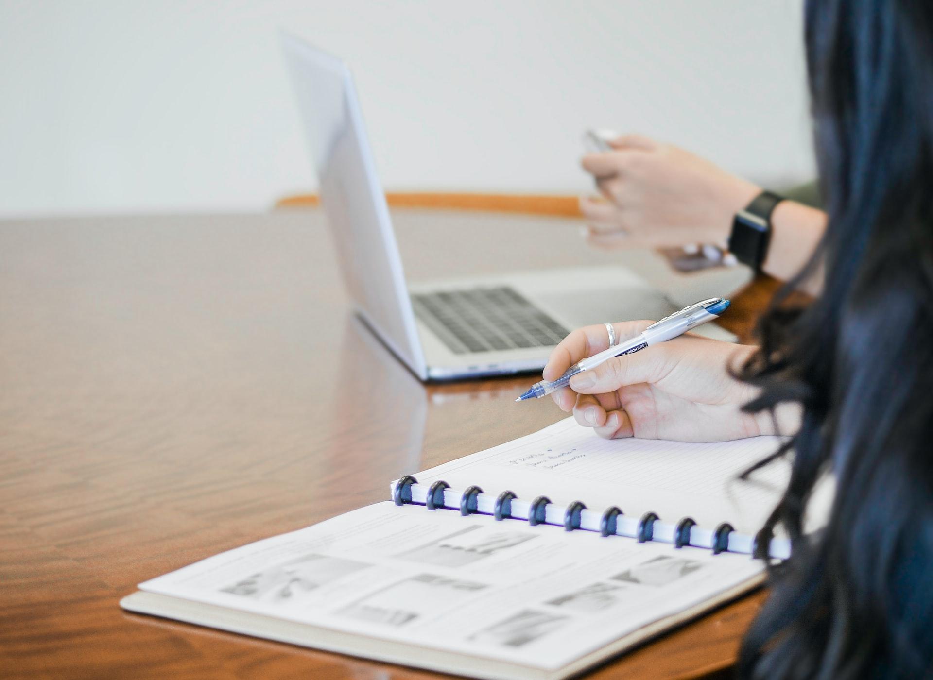 cash basis balance sheet - woman writing in a spiral notebook
